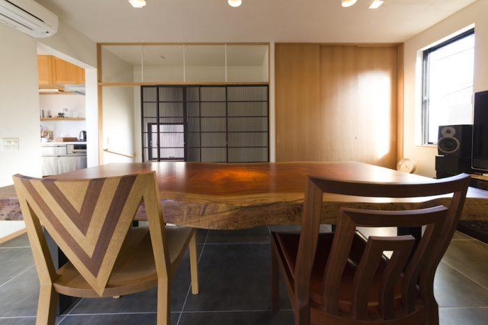 「格子戸から光が差し込む光景が好き」とご主人。無垢材を使用した椅子たちは洗練されたデザインが印象的。左奥がキッチンへと続く。