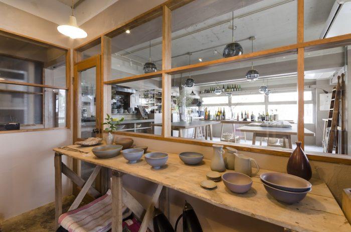 テーブルの上には「mushimegane books」の器がずらり。熊淵さんは、人と音をテーマに器作りをする陶芸家。ギャラリースペースの奥にレストランがつながっている。