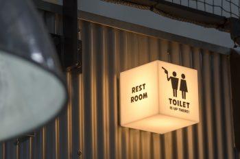 1階の壁に付けられたトイレのサイン。指がトイレのある方向を指している。使用中にはライトが点く。