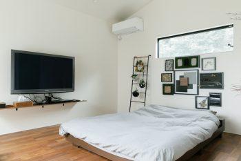 2階の寝室。緑を切り取る横長の窓と、奥さまの作品が空間に華を添える。とても落ち着くので、休日にベッドの上でテレビを見るのがご主人の至福の時なのだそう。