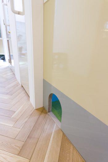 猫のトイレがある場所には、猫用ドアを。イエローとグレーのツートンカラーのドアは、コンクリート型枠用合板を使っている。
