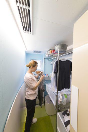 水色の壁と、芝生のような緑の床が楽しい乾燥機能がついたランドリールーム。「洗濯機の横で干してここで畳み、動線を最短にしています」