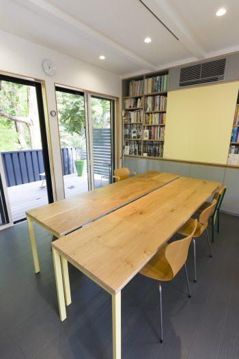 打ち合わせスペースの、分割できる240cmのテーブル。黄色のボードをスライドさせるとテレビが現れる。