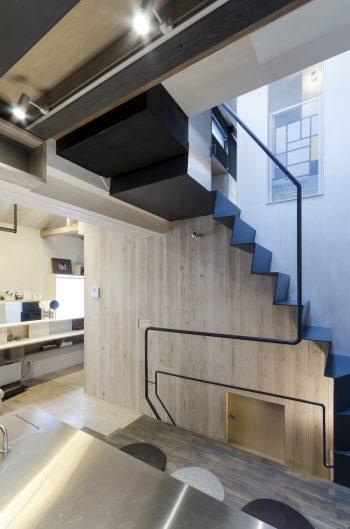 右がロフト階へ上る階段。その真下に、事務所へと通じる階段がある。