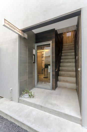 左が事務所入口。右の階段を上って左手に玄関がある。