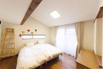 屋根なりの勾配天井と不整形な形状がユニークなベッドルーム。スリット窓は、ファサードのアクセントにもなっている。壁紙はルナファーザーを使用。