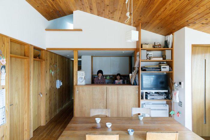 勾配天井が印象的なLDK。キッチンの上がロフトになっていて、廊下側の梯子で上り下りできる。