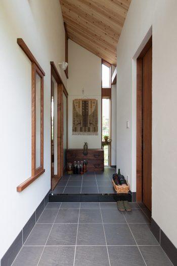 土間部分を広くとった玄関ホール。屋外から続く杉板の勾配天井やスリット窓から差し込むやわらかな光がやすらぎをもたらせる。