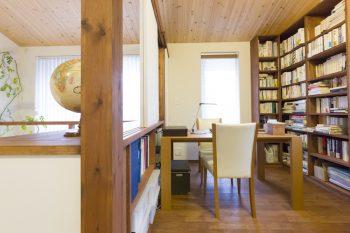杉板の天井が安心感をもたらせる書斎。天井までの本棚と吹き抜け側に設けた棚で収納たっぷり。