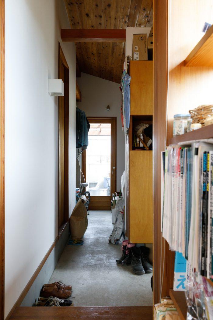 玄関を兼ねたコンクリート敷きの細長い土間には、自転車や作業着なども収納。