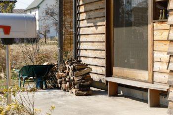 外壁の脇に出番を待つたくさんの薪が。写真右の窓の近くに薪ストーブが置かれているため、薪をすぐに取りに行ける。