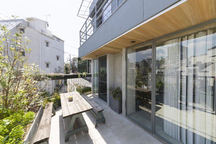 ガラス張りのオープンな玄関。脇にはテラスがあり、食事をしたりバーベキューを楽しむことも。
