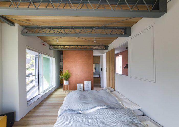 鉄骨とラワン、銅粉…。異素材の組み合わせが絶妙な3階のベッドルーム。ベランダの手すりには、オーダーで作った鉄のプランターに花が咲く。