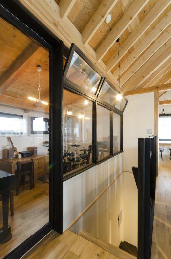 リビングと音楽室はクリアガラスの窓でゆるやかに隔てられている。