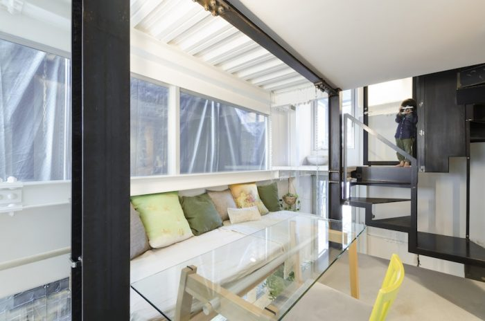 1階のミーティングスペース。カラフルなクッションの置かれたベンチは吹き抜け部分に吊られている。この場所は吉田家の第2のリビングスペースとしても使われているという。