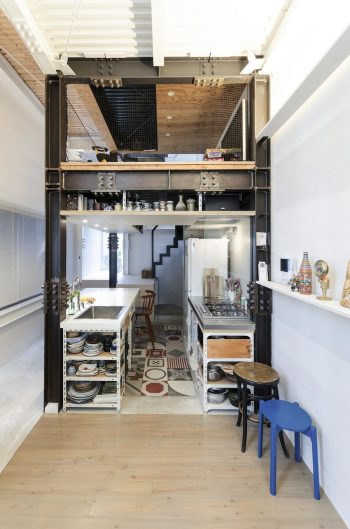 リビング部分からダイニングキッチンとロフトを見る。フローリングとタイル、土間と場所により床の素材を変えている。