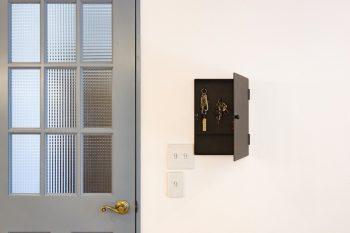 玄関へと続くドアは、白木にブルーグレーの塗料をペイント。右側は、アイアン製のオリジナルキーボックス。