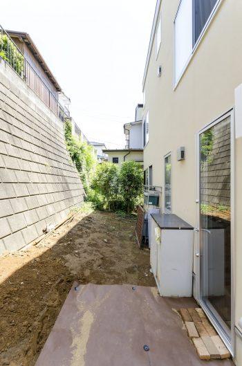 市の崖条例により背後の擁壁との間に距離を取る必要があった。これによりガーデニングも可能な広めの裏庭ができた。