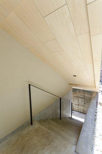バイクガレージの隣につくられた階段。家を2棟に分離しているため、階段を上がったこのレベルも1階扱いとなる。