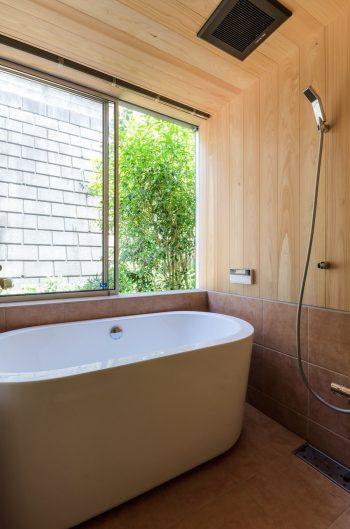 馬場さんからヒノキにしたいと要望のあった浴室。ヒノキ系のサワラを張り、下部はそれと色味が合うタイルを採用した。