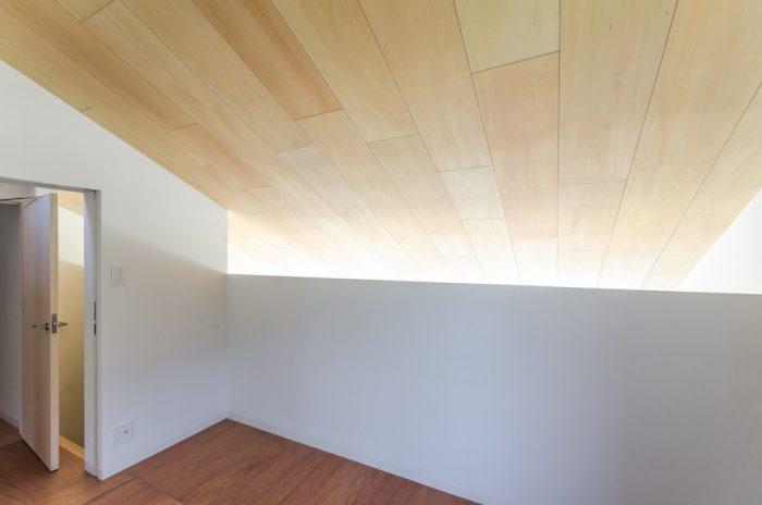 1階のハイサイドライトから入った光が斜めの天井を伝って2階を明るく照らす。