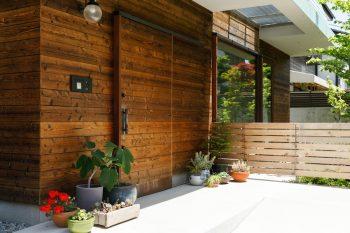 玄関扉は引き戸。右手の木柵の奥に庭がある。造園屋さんに頼んで小道をつくり、その周りに山野草などを植えてもらった。