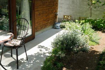 軒下にはテーブルと椅子を置いている。写真左の窓を開けると、土間、軒下、庭が段差なくつながる。