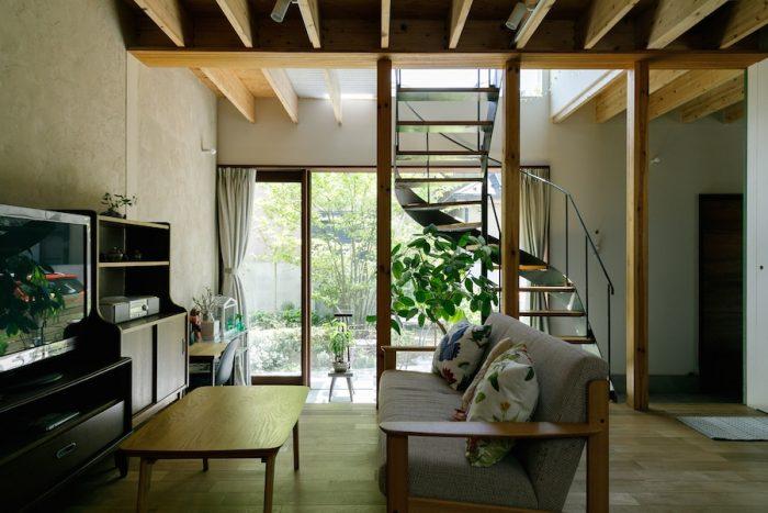 """リビングから土間、庭を見る。庭の中央には""""帽子の家""""にちなんだシンボルツリー「ヤマボウシ」の姿が。写真左手の壁は、DIYで珪藻土を塗って仕上げた。"""