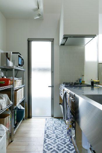 背面に造作収納をつくらず、ステンレスの棚に家電や鍋類、食器などを収納。扉がないため圧迫感がなく、軽やかな印象だ。