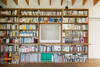 壁一面の書棚には、記者であるご主人の蔵書がびっしり。中央の開口部は吹き抜けとつながっていて、空気の循環や採光に役立つ。