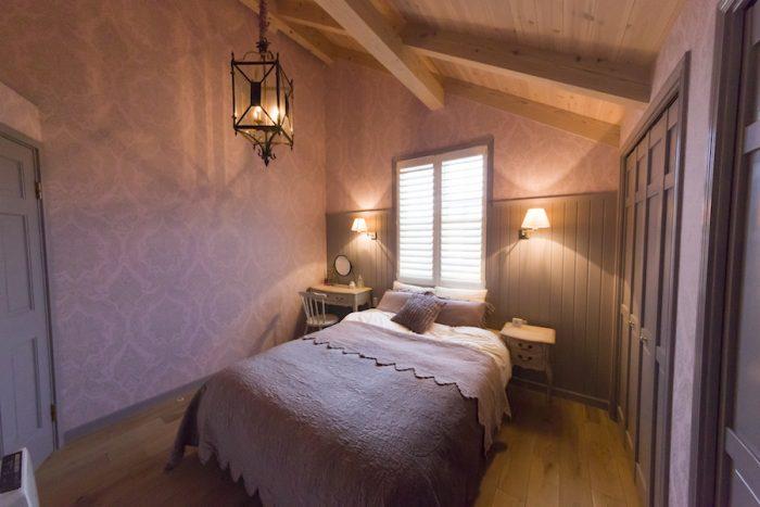 紫がかったベージュのクロスに合わせたコーディネートで、落ち着く雰囲気のベッドルーム。窓には風の向きを調整できるNORMANのウッドシャッターを設置。