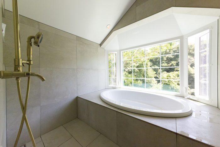 窓の向こうに絶景が広がるバスルーム。シャワーはKOHLER。レインシャワーも併設して贅沢に。