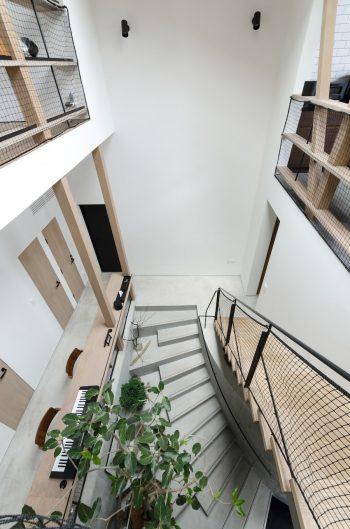RCの階段がゆるやかにカーヴする。地下から2階の天井まで吹き抜けた開放的な空間。
