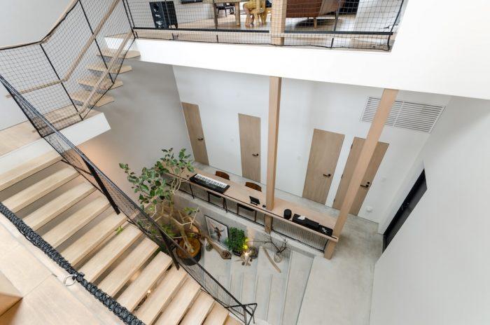 キッチンから見下ろすとこのように見える。1・2階の柱には、梁の色と合わせるために赤味のある材に薄い単板が貼られている。