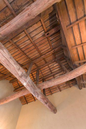 2階の寝室は天井を抜き、年代ものの迫力のある梁が露わに。柔らかな色合いの壁は藁を混ぜた珪藻土。