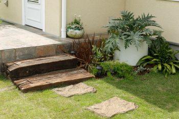 毎日の「行ってきます」「ただいま」を見守る古材の階段と飛び石。