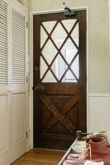 二重扉の玄関は、風除けや防寒に効果大。重厚な内ドアは、アメリカの古い家にあったもの。深みのある色合いが美しい。