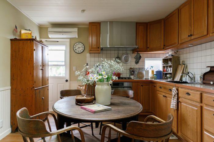 ダイニングキッチン。くの字型に配したカウンターや収納は、作業のしやすさを考え抜いてオリジナルで造作したもの。シンクはユーズドを使い、コストを抑えた。勝手口のドアは、網戸にできて風が抜ける仕様のものに。