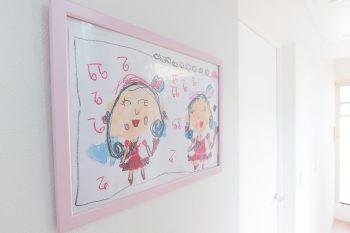 屋上へ抜ける明るい廊下には、娘さんたちが描いた絵が飾られている。これは、次女さんが自分とお姉さんを描いたもの。