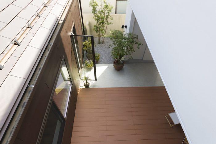 屋上からアウトドアリビングを見下ろす。右側の白い壁に南側からの光が反射し、さらに明るさをもたらす。