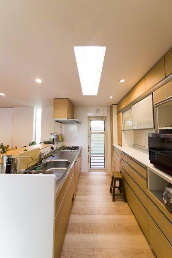 トップライトからの光も入る明るいキッチン。奥の勝手口を開けると、一時的にゴミも置ける。防犯面から、人感センサー付きライトを設置してもらった。