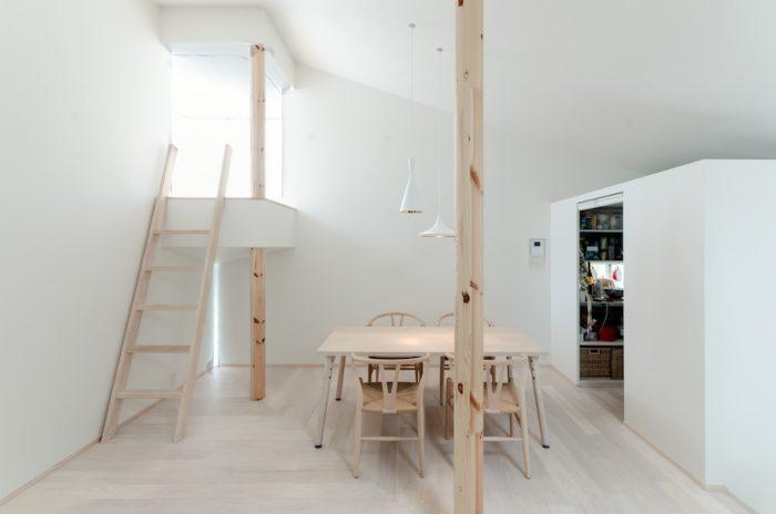 2 階のリビングダイニング。左にロフト、右にキッチンがある。白を基調にした室内に淡い色味の木が使われている。フローリングにはバーチ材を使用。ダイニングテーブルはこの家のためにオリジナルでつくられたもの。