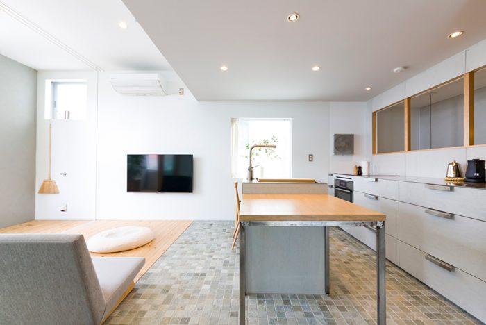 キッチン側は天井高を低くして、落ち着ける雰囲気に。シンクを設置したアイランド横のテーブルは、タモ材の天板に鉄骨の脚でオーダーしたもの。
