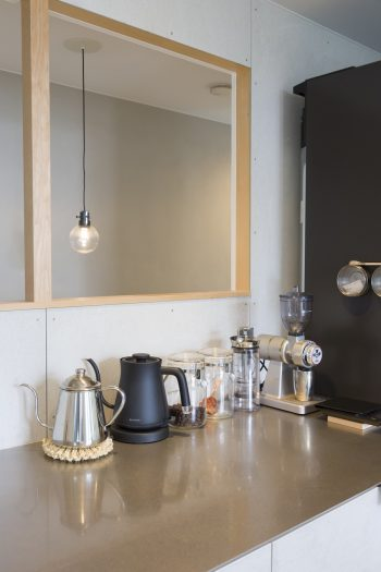 キッチンの壁に開口を設けて階段ホールと接げ、奥行きを出した。自宅でもコーヒーを楽しむそう。