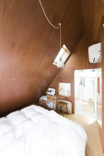 ベッドルームは素朴な風合いのラワンベニヤで。右側にリネンのカーテンで仕切ったクローゼットがある。