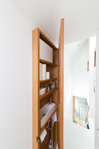 トイレのドアを閉めると現れる収納。限られた場所を有効に使うアイデア。