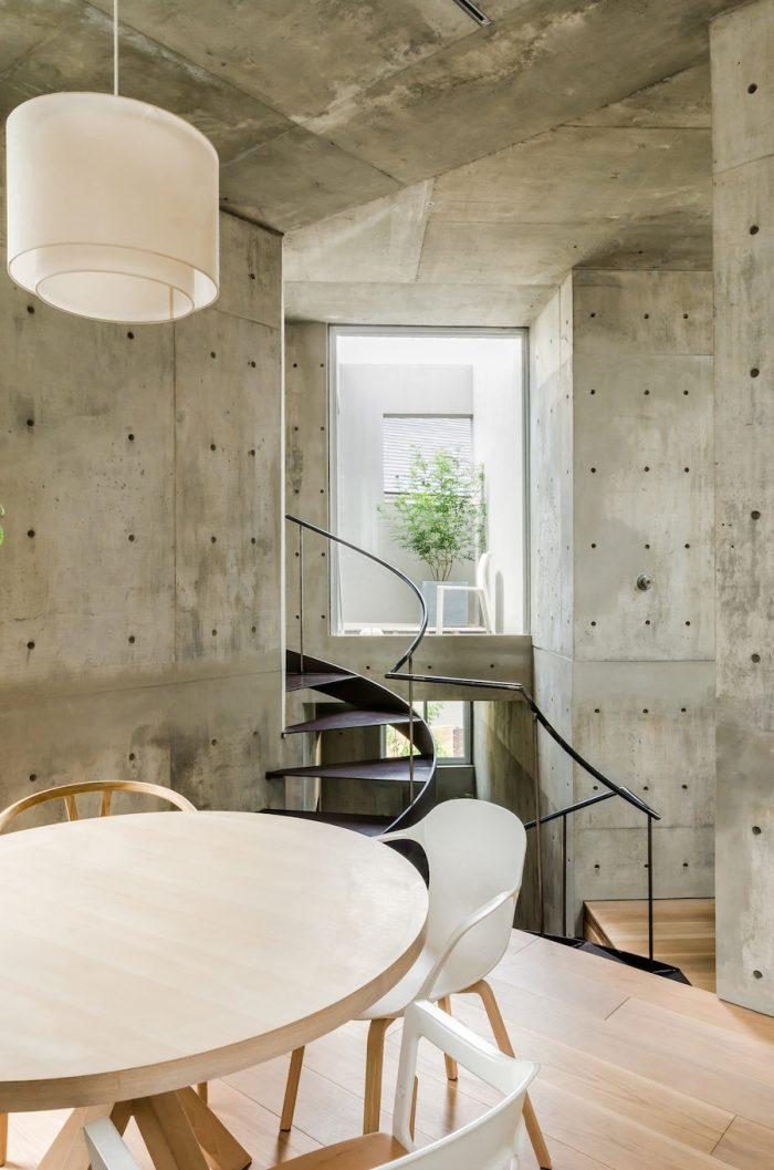 2階のダイニングからテラスを見る。粗い仕上げのコンクリートの壁・天井が印象的な住空間。幅広のフローリングはオーク材をホワイトオイルで仕上げている。