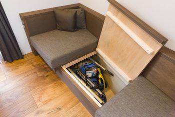 変形地に沿って造作したソファは収納も兼ねている。高低差のある敷地を活かし、床下40cmの大容量の収納を確保した。