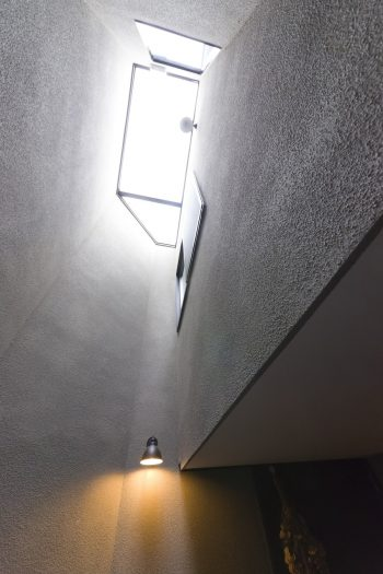 玄関内部は窓がなく、吹き抜けの上部にトップライトがあるのみの薄暗い空間。