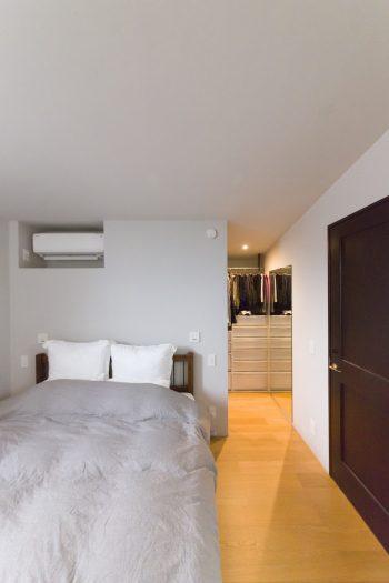 屋根なりの天井が落ち着きをもたらす主寝室。奥がウォークインクローゼット。壁を珪藻土にしてカビを予防。